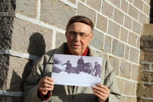 Monsenhor Blevio Oselame segura a fotografia que registra o esforço dele e de amigos para desatolar o jipe na neve